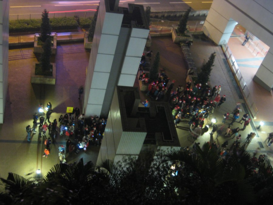 xmas eve outside Hang Hau MTR [view from our balcony] - the city is full of carol singing groups battling for supremacy, the one with the brass band seems likely to win