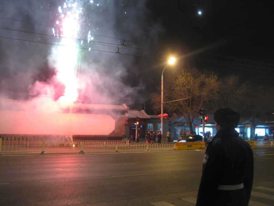 one of the security guards observes fireworks across the road from our apartment on the street