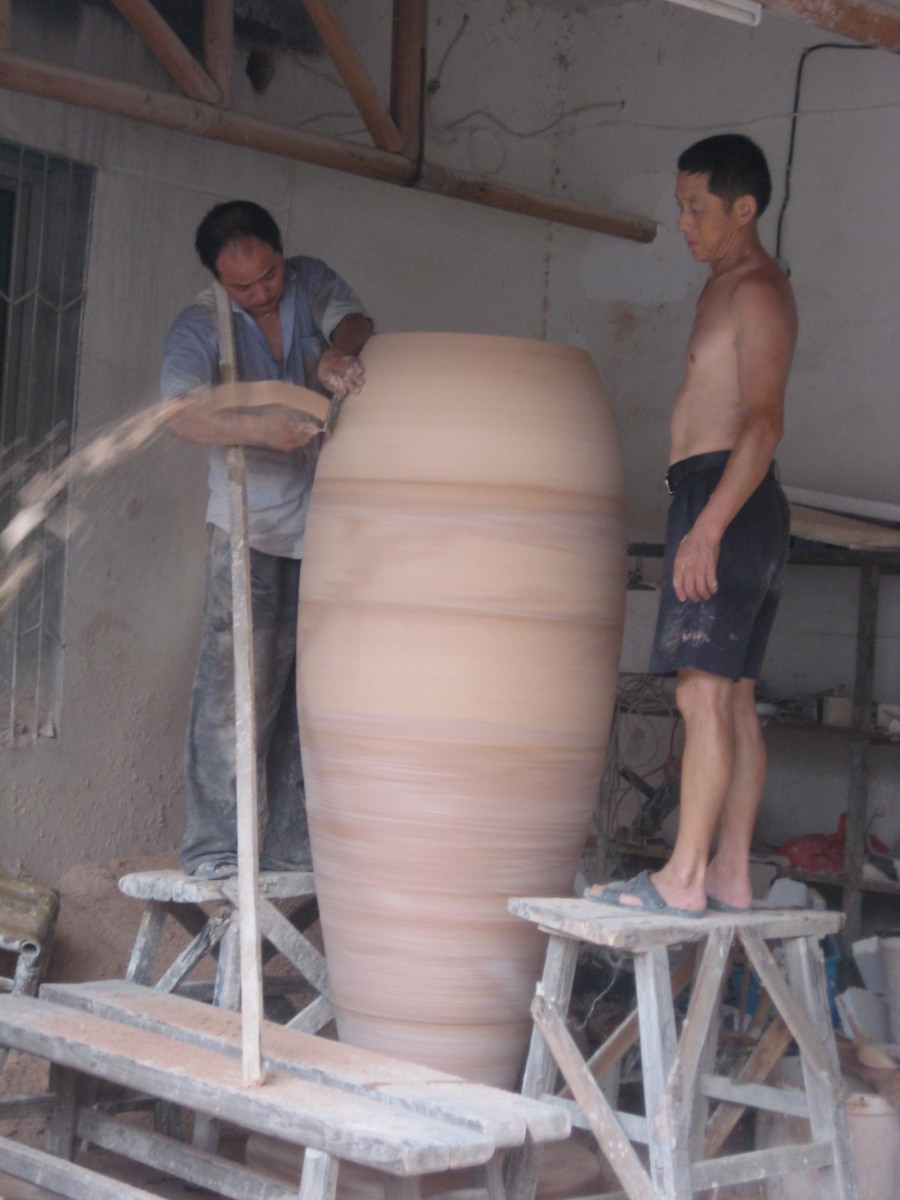 making giant pots, connecting sections requires a team of workers [usually topless men with cigarettes]